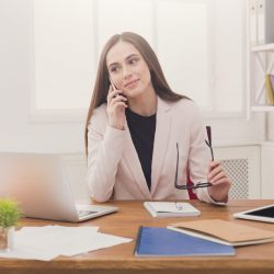 Young business woman talking by phone at modern office copy space. Business consulting.